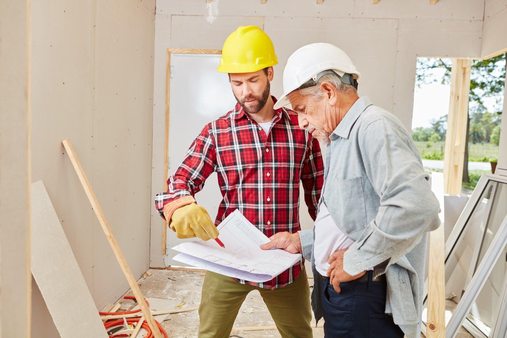 dwóch mężczyzn ogląda plan budowy domu