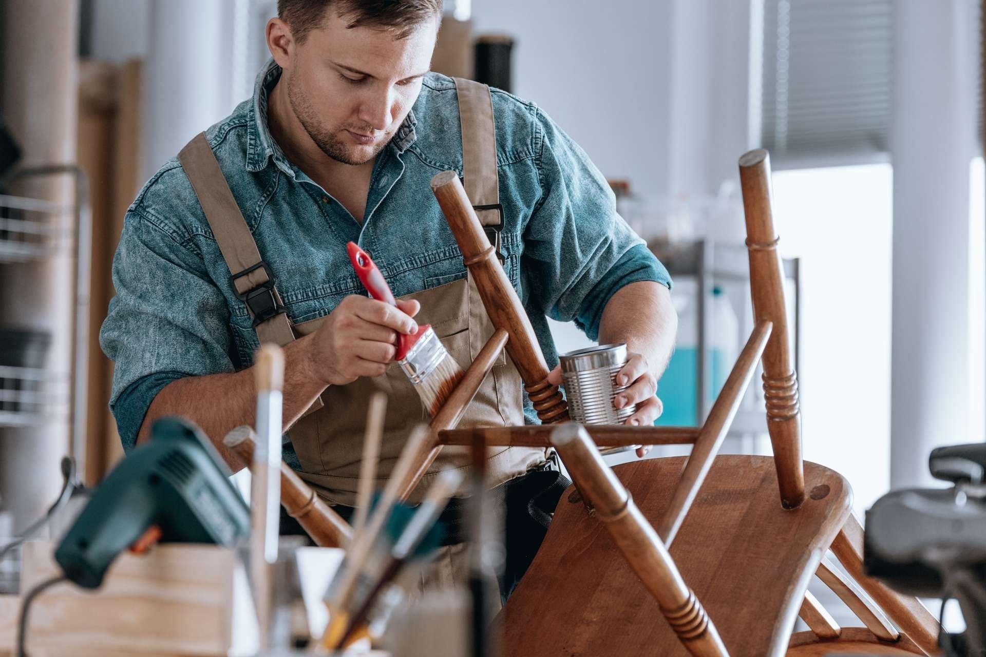 mężczyzna maluje nogi krzesła