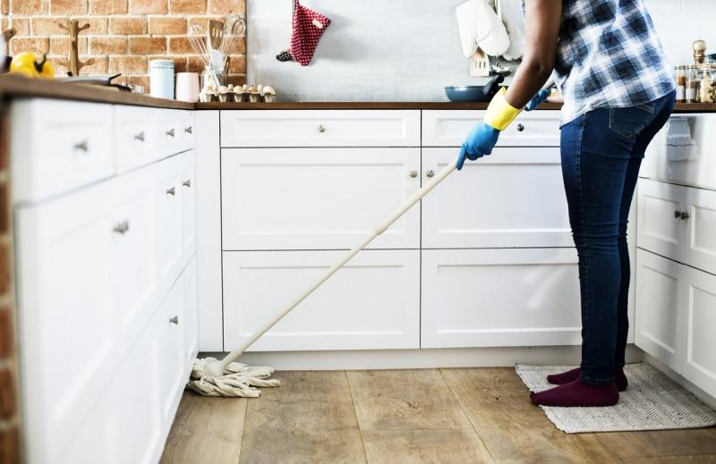 kobieta myje podłogę wkuchni