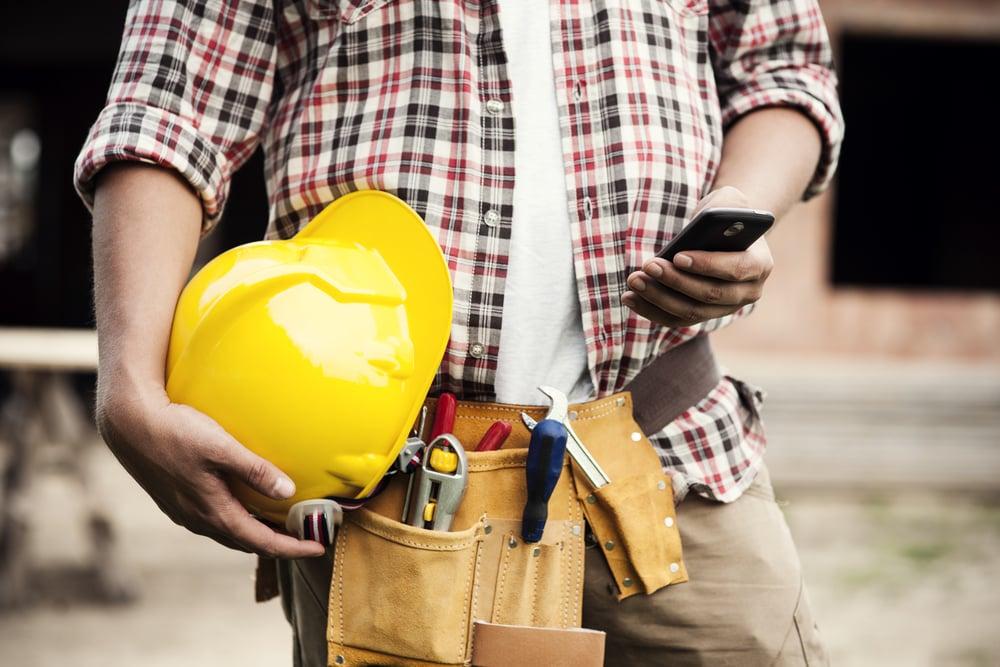 robotnik budowlany trzyma telefon i żółty kask