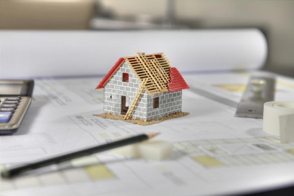 plany architektoniczne i miniaturka domu na stole