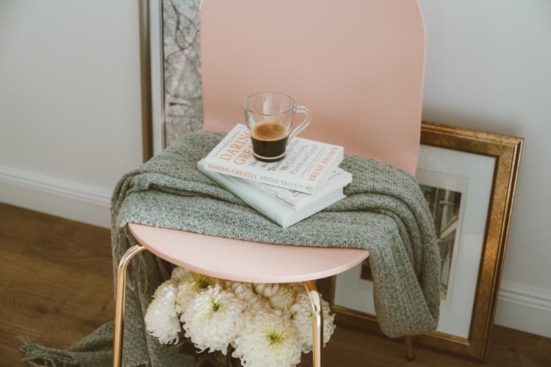 różowe krzesło zkocem ksiazka kawa ikwiatami