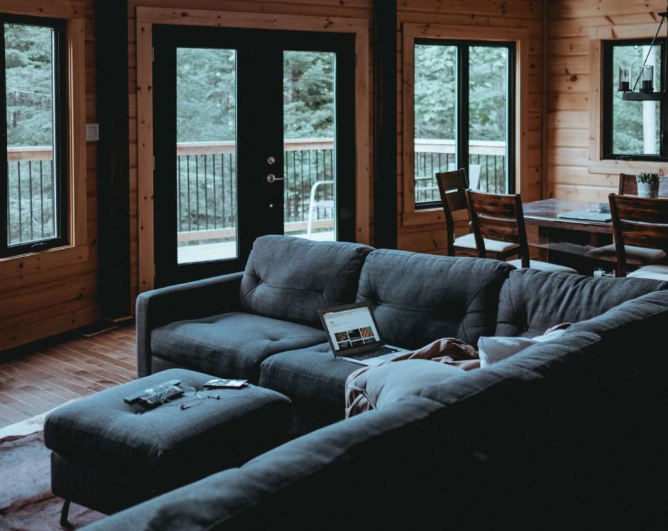 szara kanapa ikrzesła wdrewnianym pokoju