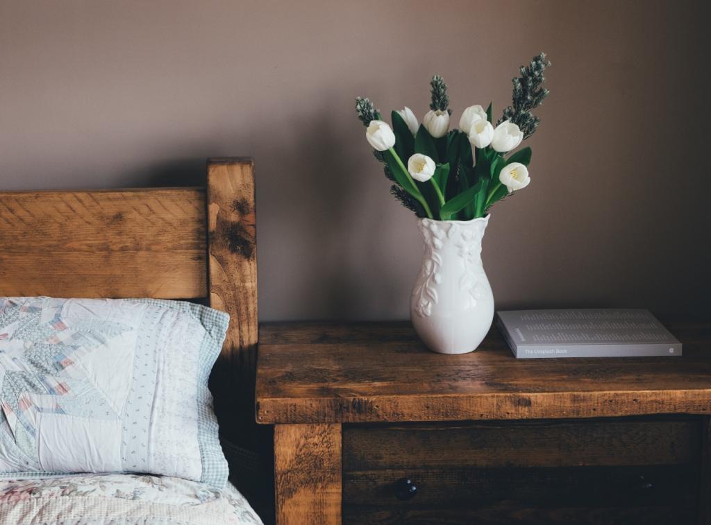 drewniane łóżko ibiałe kwiatki