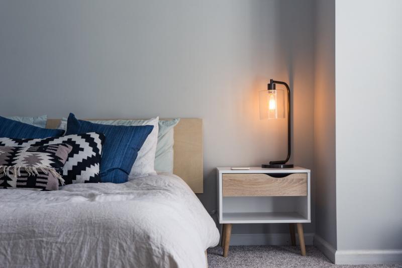 łóżko zkolorowymi poduszkami izapalona lampka nocna