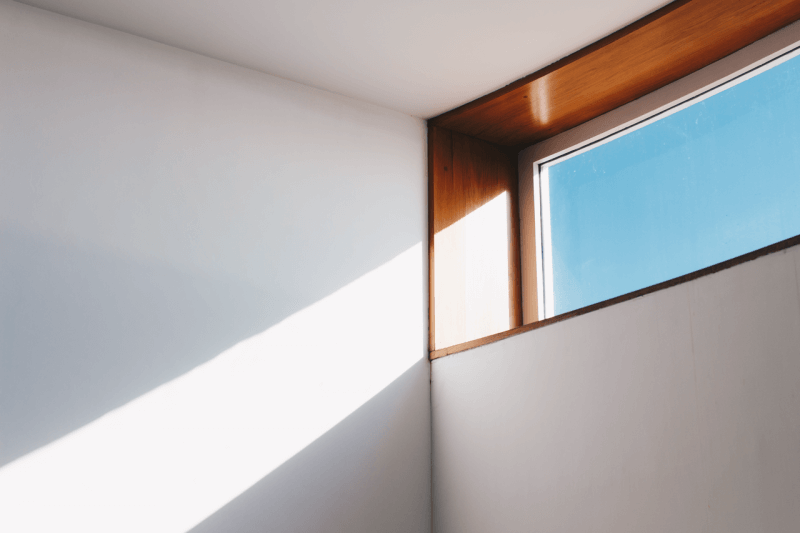 drewniane okno i biała ściana