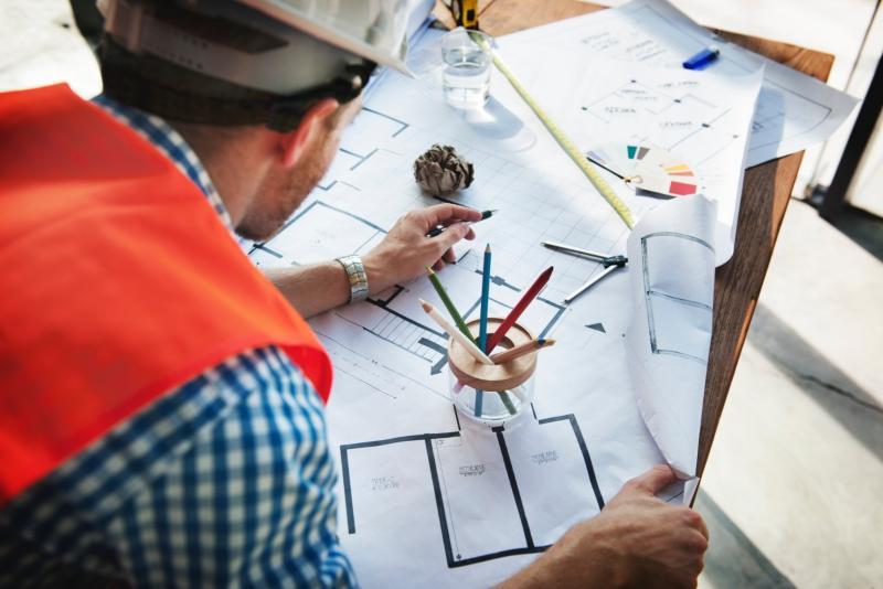 robotnik patrzacy na plan budowy domu