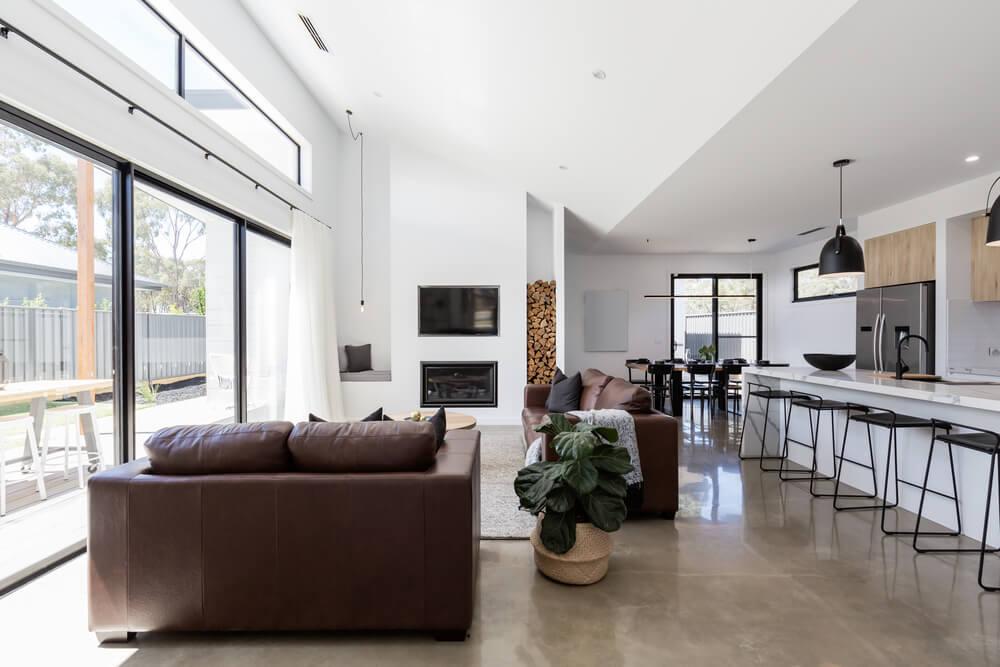 przestronny salon zdużym oknem ibetonową podłogą
