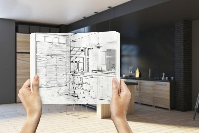 ręce trzymają zeszyt zrysunkiem wnętrza kuchni