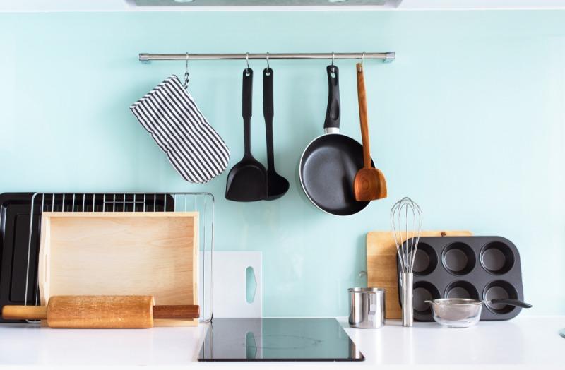 niebieska ściana wkuchni zprzyborami kuchennymi