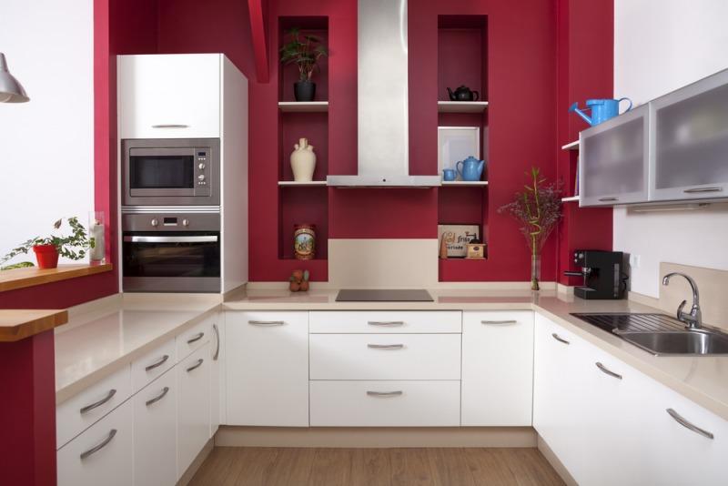 kuchnia zczerwoną ścianą ibiałymi meblami