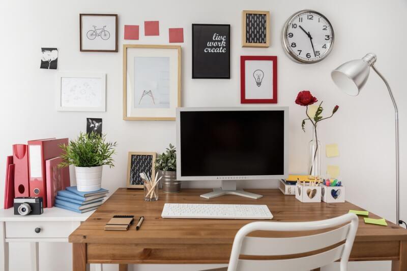 drewniane biurko z monitorem i obrazami na ścianie