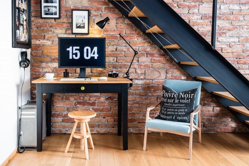 biurko podschodami zcegłą naścianie