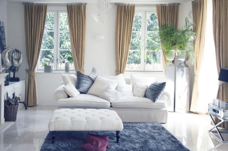 jasny salon zbiałą kanapą iniebieskim dywanem