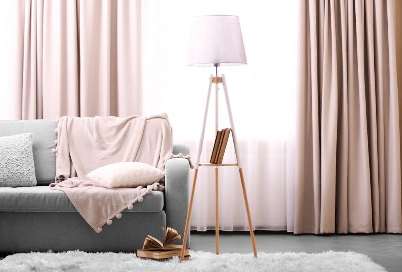 szara sofa różowe zasłony i lampa strojąca